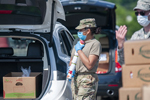 U.S. Army Pfc. Stephanie Huertas, a motor transport operator with the Delaware Army National Guard's 1049th Transportation Company, carries a stack of cans at a drive-thru food pantry on the grounds of Dover International Speedway in Dover, Delaware, June 24, 2020. Capt. Brendan Mackie